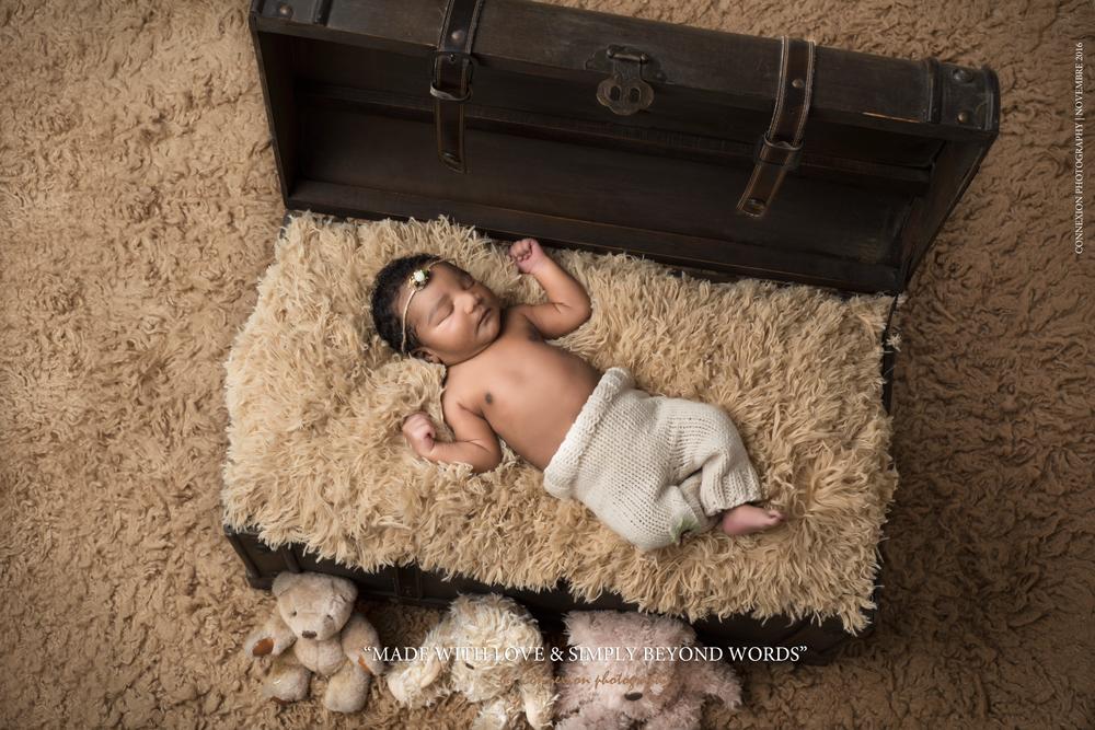 Bébé noir torse nu endormi dos sur fourrure beige dans une malle