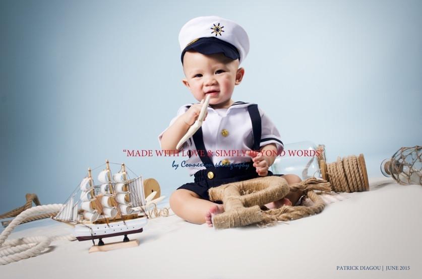 Bébé blanc en tenue de marin avec képi,souriant assis sur le sol dans un décor marin sur fond bleu