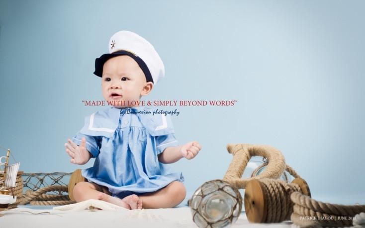 Bébé blanc en tenue de marin bleue et un képi, assis dans un décor marin avec fond bleu