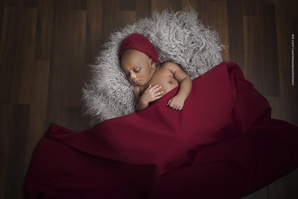 bébé noir endormi sur le dos a moitié couvert d'un drap rouge sur une fourrure beige