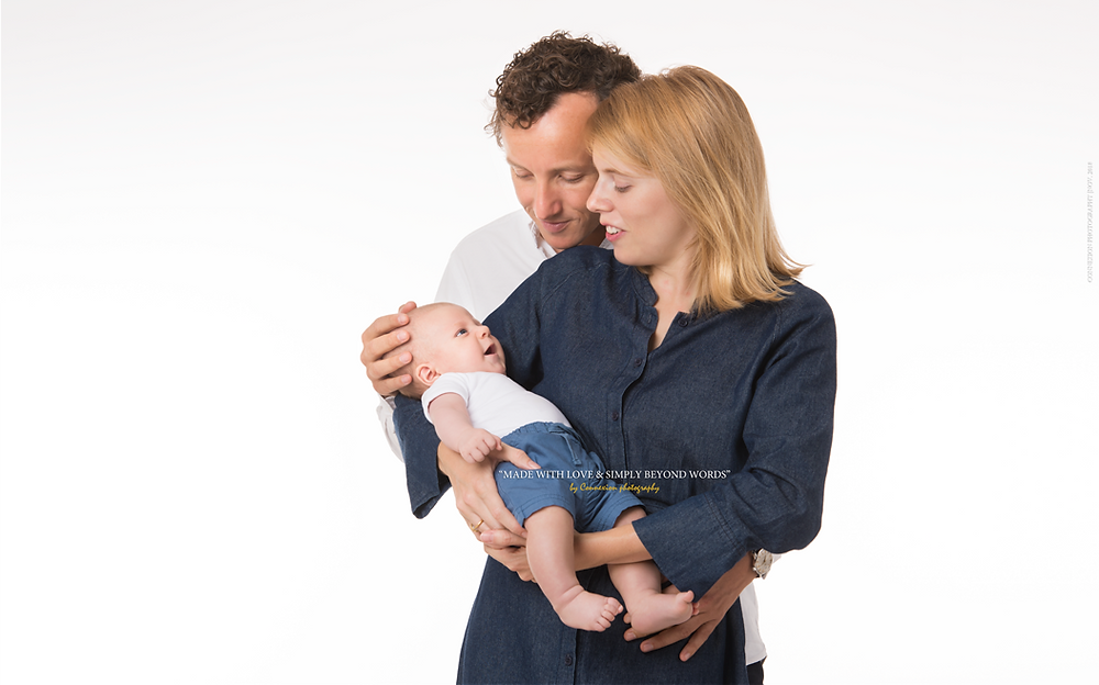 Famille de blancs debout sur fond blanc bébé dans les mains de maman et papa à l;arrière