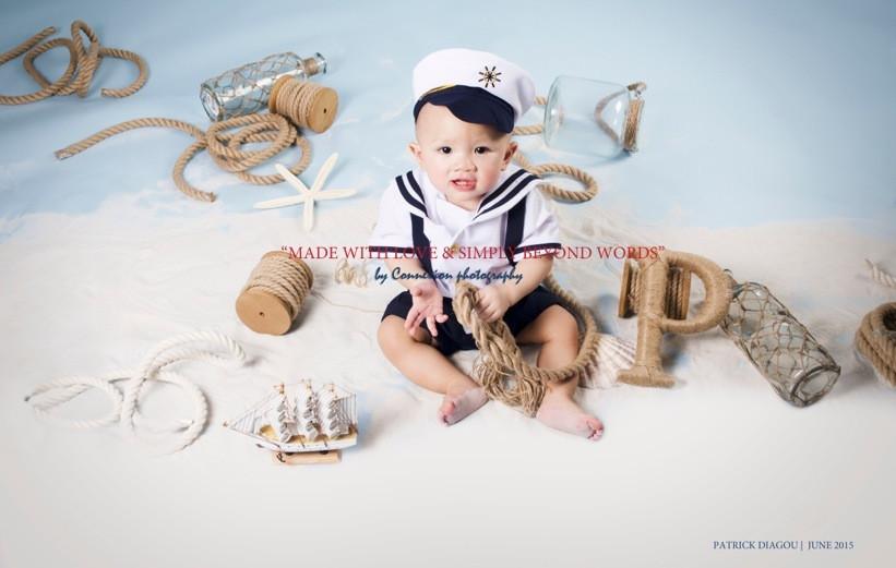 Bébé blanc en tenue de marin avec képi,souriant corde à la main, assis sol dans un décor marin sur fond bleu