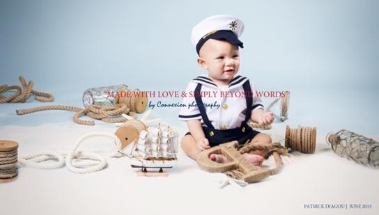 Bébé blanc en tenue de marin avec képi,souriant assis sur le sol, légèrement de profil dans une décor marin sur fond bleu