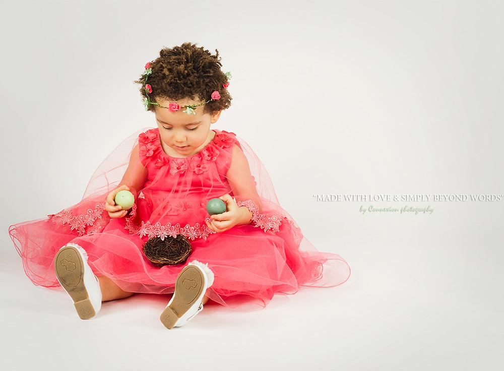 Petite fille metisse assise jouant avec des oeufs