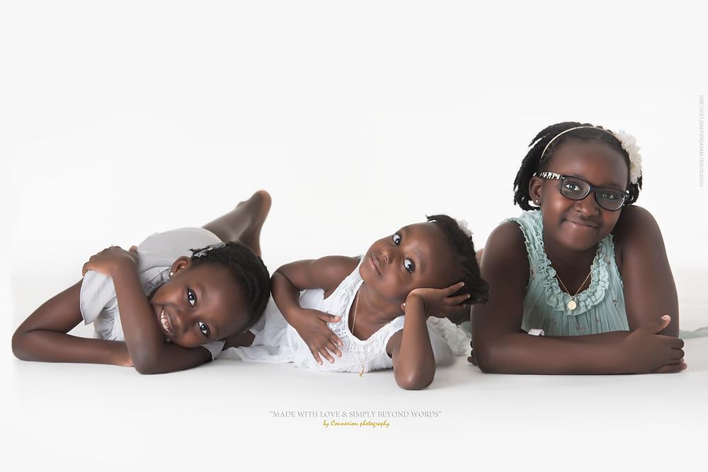 trois petite filles noires couchées sur n fond blanc