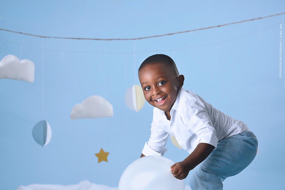 Enfant noir accroupi sur fond bleu tente de prendre un ballon en souriant