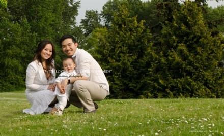 Petite famille chinoise avec enfant entre papa et maman à moitié assis