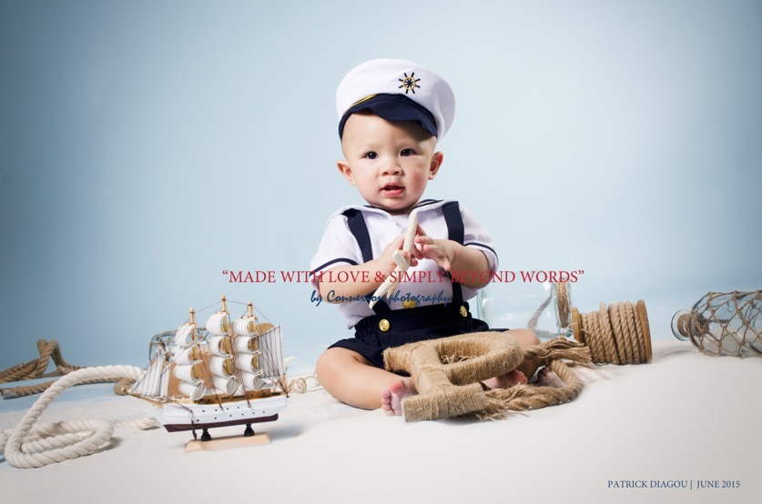 Bébé blanc en tenue de marin avec képi, assis dans un décor marin sur fond bleu