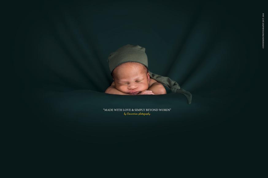 Bébé noir couché sur un fond vert de face la menton sur les bras croisés