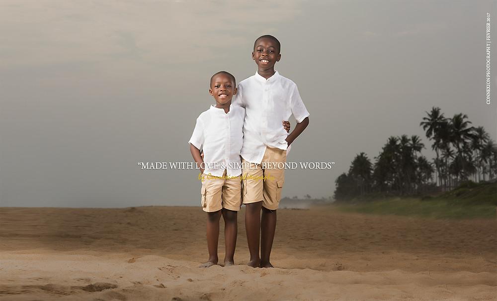 deux enfants noirs debout souriant sur le bord de mer