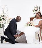 couple de mariés noirs, l'homme à genoux chausse sa femme