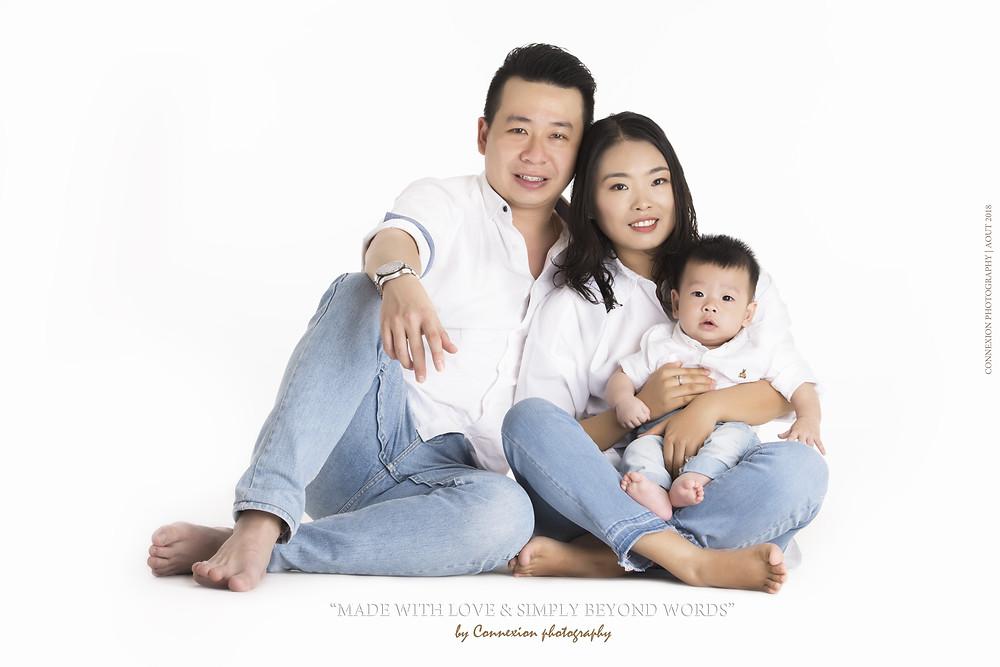 Petite famille asiatique assise sur fond blanc