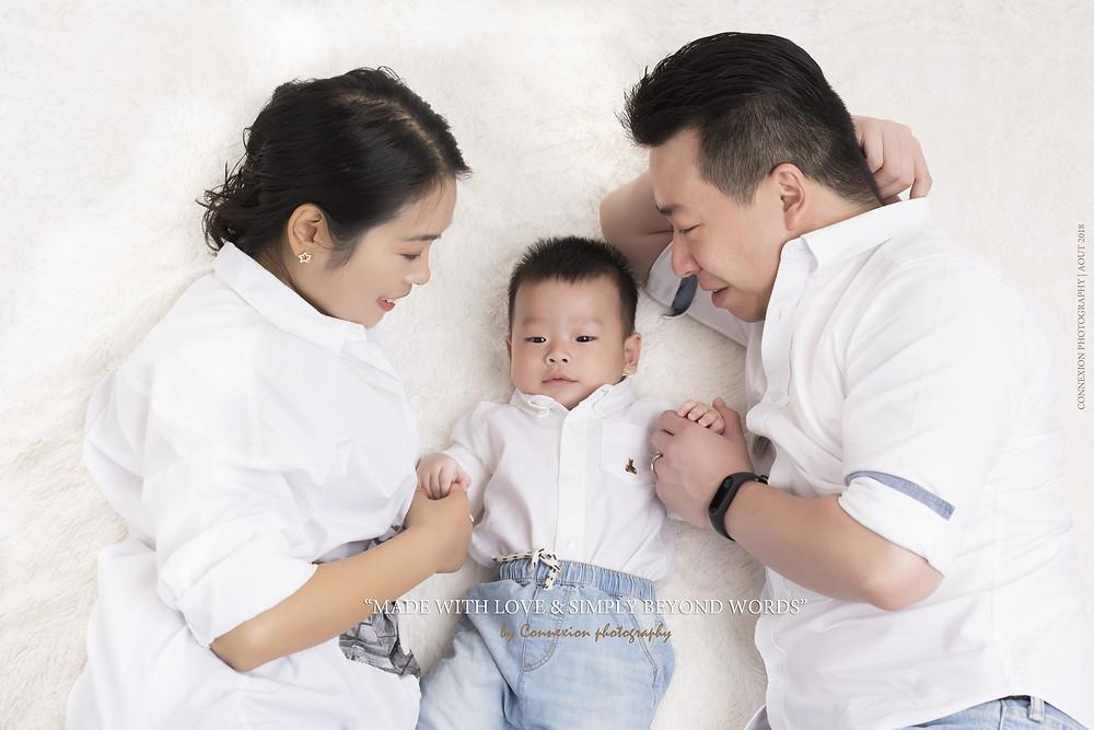 Petite famille asiatique couché sur fond blanc