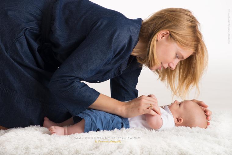 Maman blanche à genou au dessus de son bébé couché sur une fourrure blanche