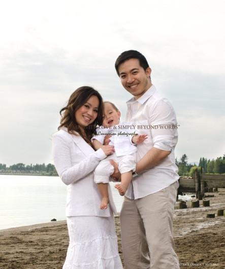Petite famille chinoise au bord de l'eau avec enfant entre papa et maman