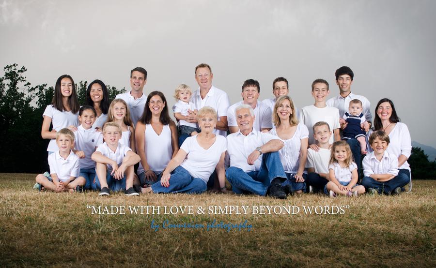 Portrait d'une grande famille blanche tous vêtu de blanc et bleu, assis dans un parc