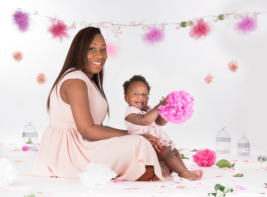 Maman et sa petite fille noir assisent dans un décor de palette de couleurs violet et saumon