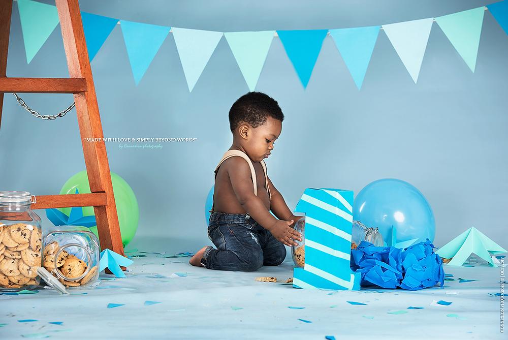 Enfant noir jouant dans un décor d'anniversaire bleu
