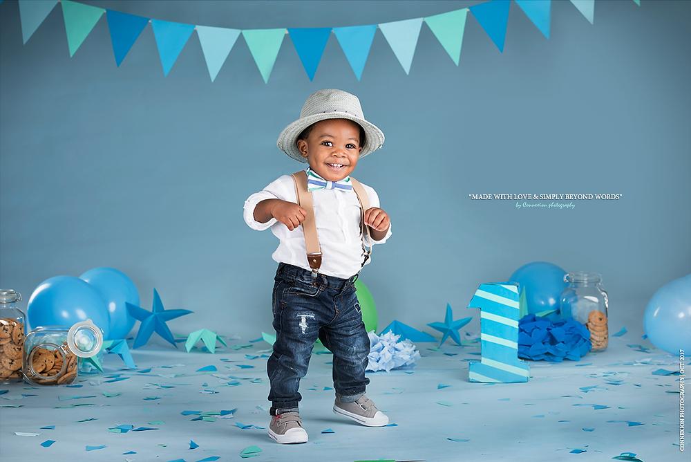Enfant noir vêtu d'une salopette, une chemise blanche et un chapeau debout souriant sur fond bleu
