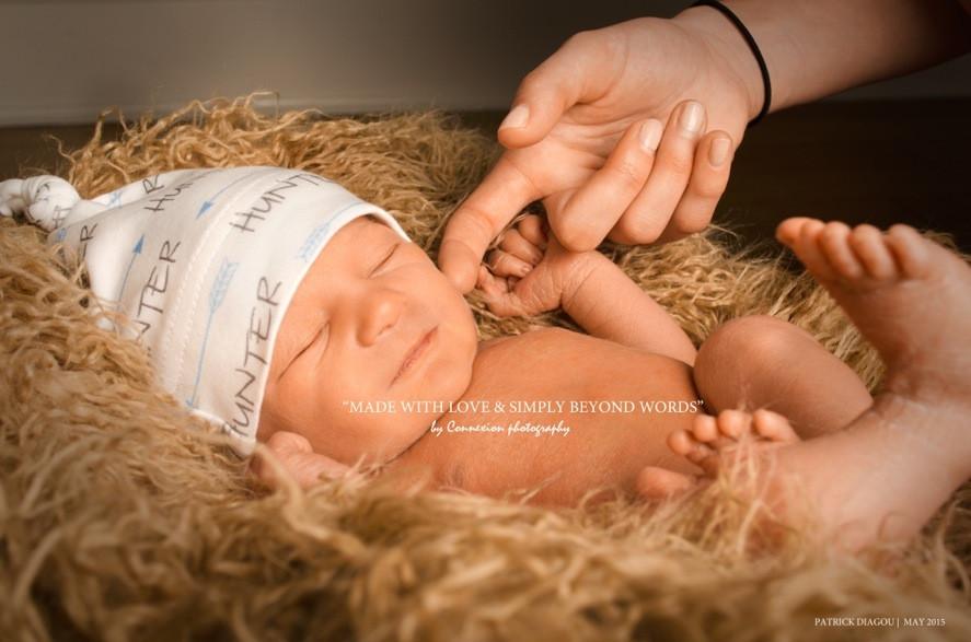Bébé blanc avec bonnet blanc endormi sur fourrure beige sourit au contact du doigt de maman contre sa joue.