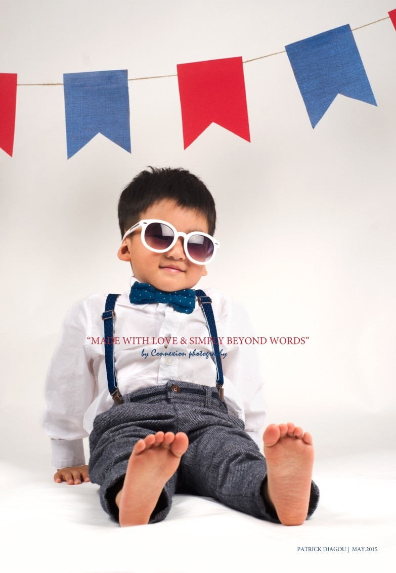 Enfant asiatique assis sur le sol en tenue de soirée avec des lunettes de soleil