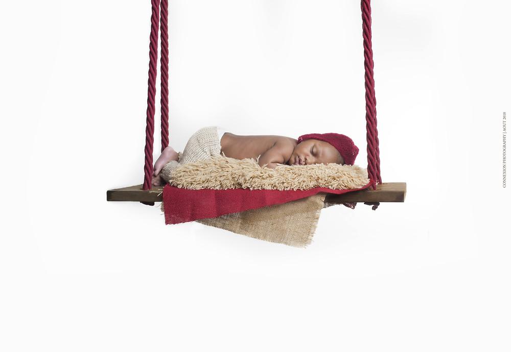 bébé noir endormi sur une balançoire