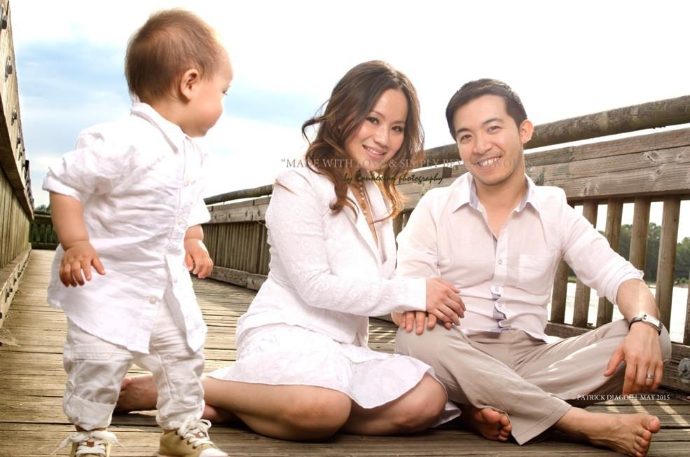 Petite famille chinoise sur ponton dans un parc, enfant debout