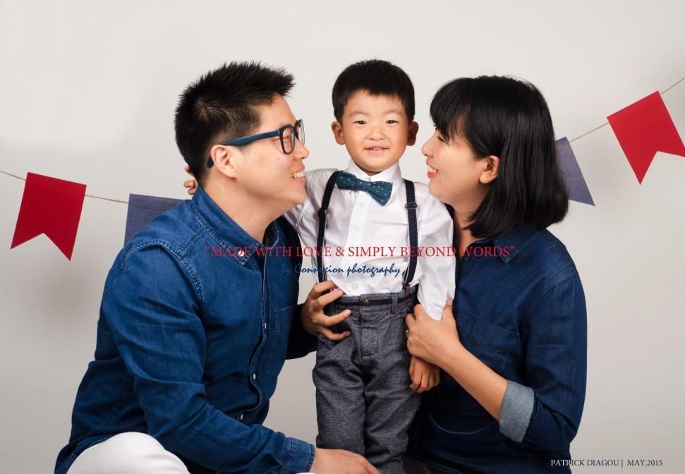 Petite famille d'asiatiques, papa et maman assis  sur le sol regardent leur enfant debout entre eux
