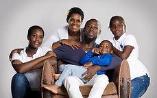 Famille noir reunie autour de papa assis dans un fauteuil