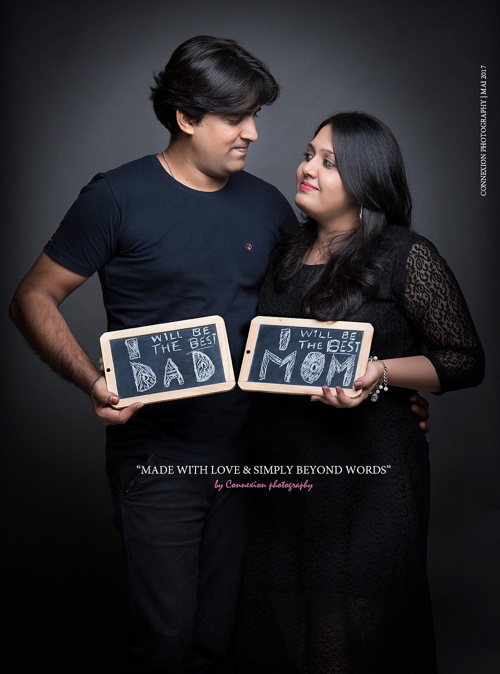 homme avec femme enceinte debout se regardant avec des ardoises en main