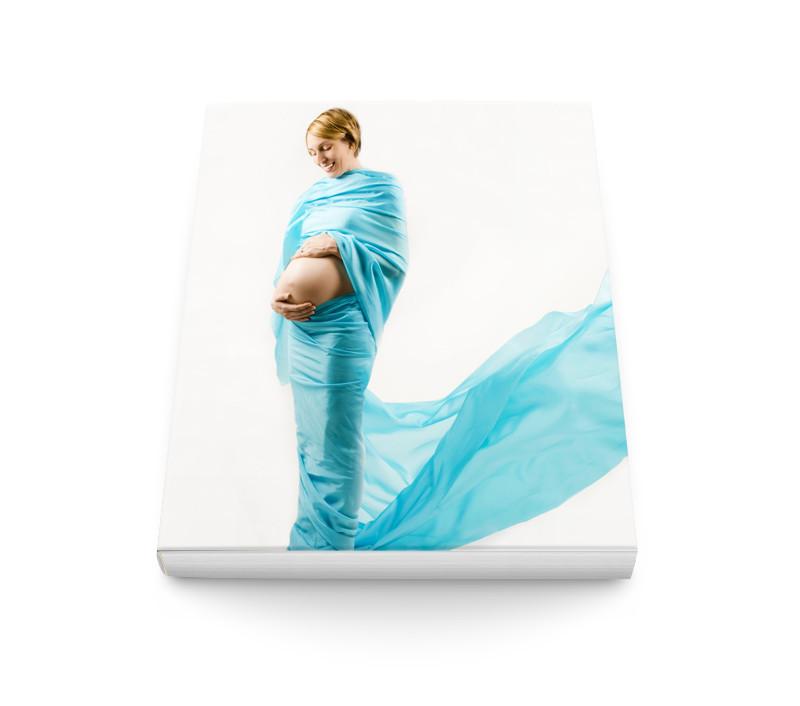 Livre photo prénatal avec Femme enceinte blanche enroulée d'un long tissus bleu, le ventre à découvert, sur la couverture