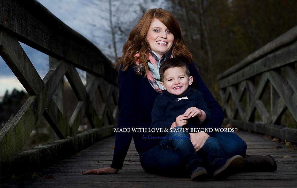 Maman blanche assise sur un ponton avec son enfant sur les pieds