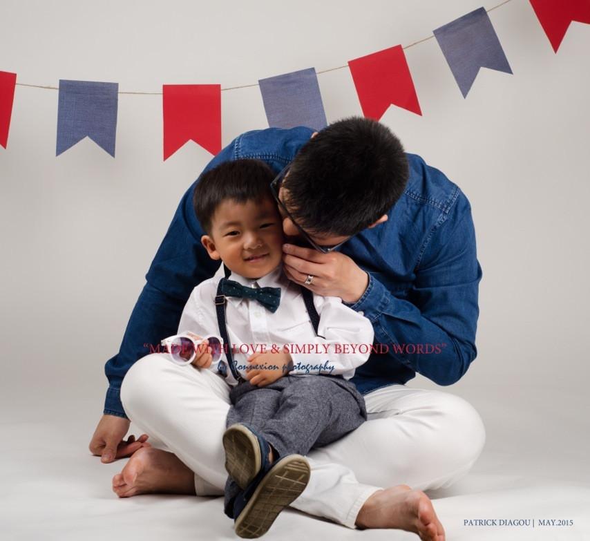 Papa asiatique embrasse la joue de enfant assis sur ses pieds à même le sol