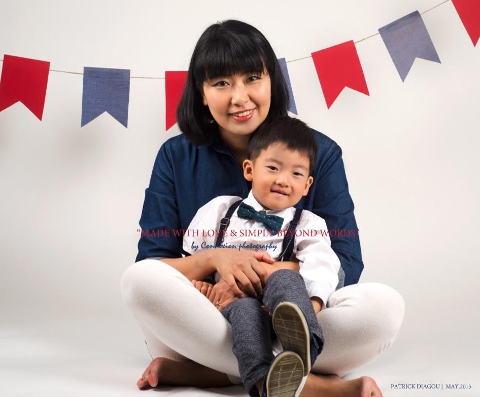 Maman asiatique assise sur le sol son enfant sur ses pieds