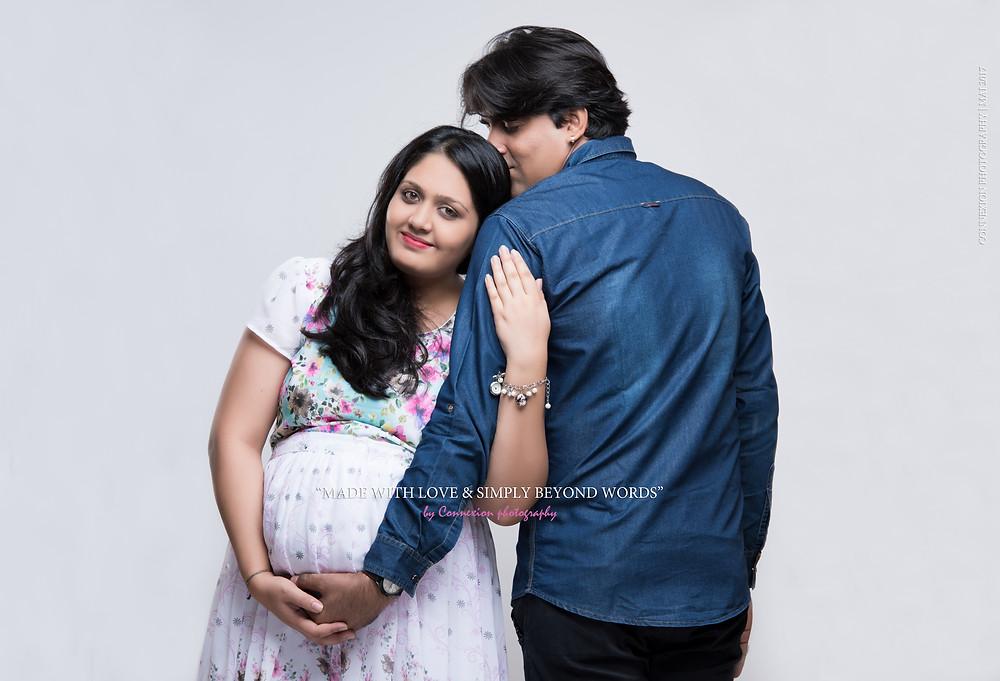 couple de pakistanais debout la tête de la femme enceinte contre l'épaule de son mari qui tient son ventre