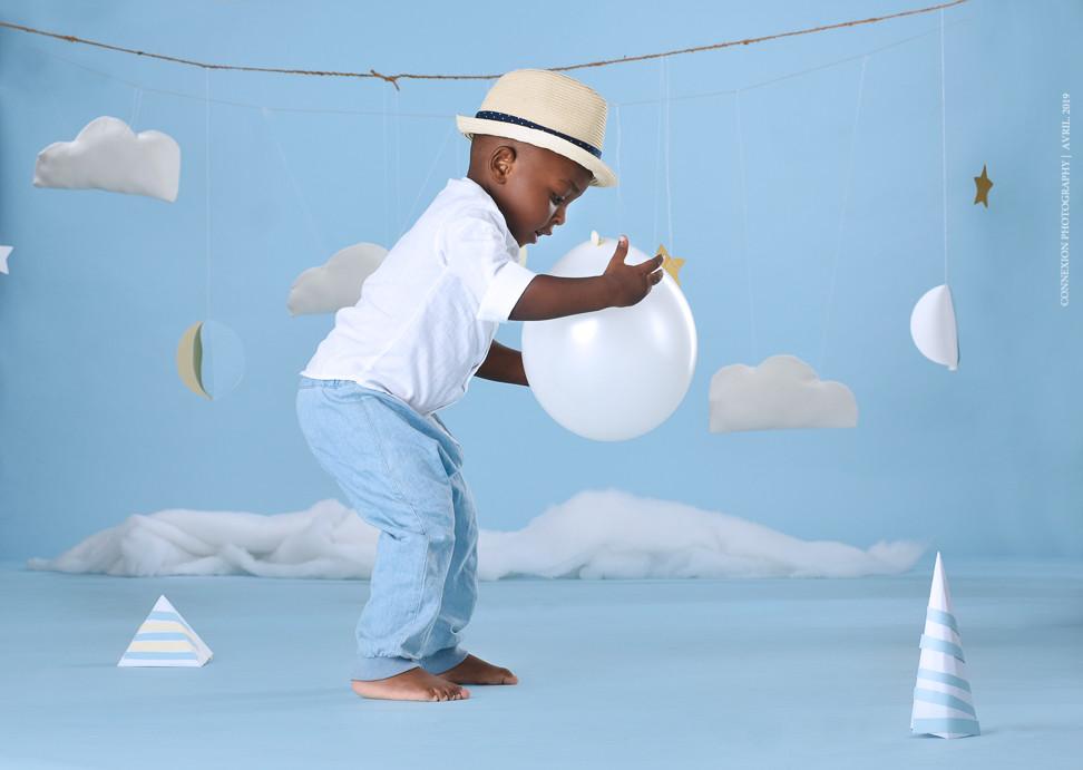enfant noir debout sur fond bleu tient un ballon entre ses mains.