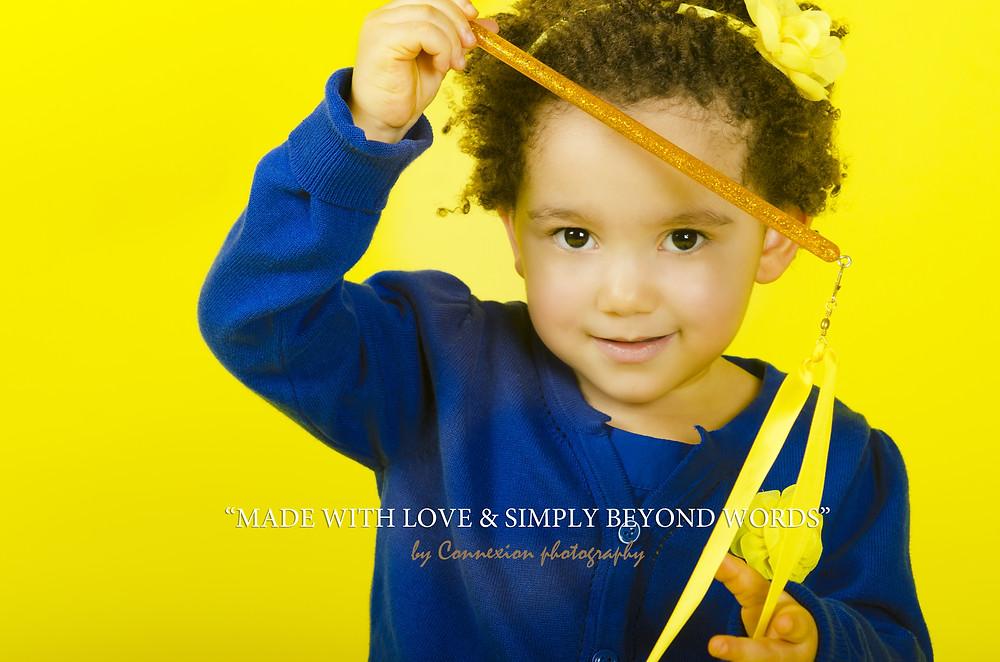 petite fille métisse sur fond jaune un jouet à la main