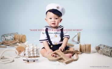Bébé blanc en tenue de marin avec képi,souriant assis sur le sol dans un décora marin fond bleu