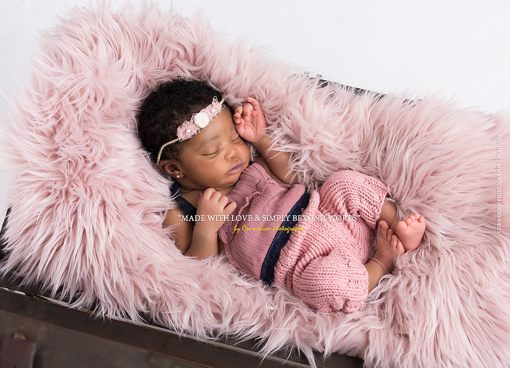 bébé noir dormant sur une fourrure rose posée dans une malle