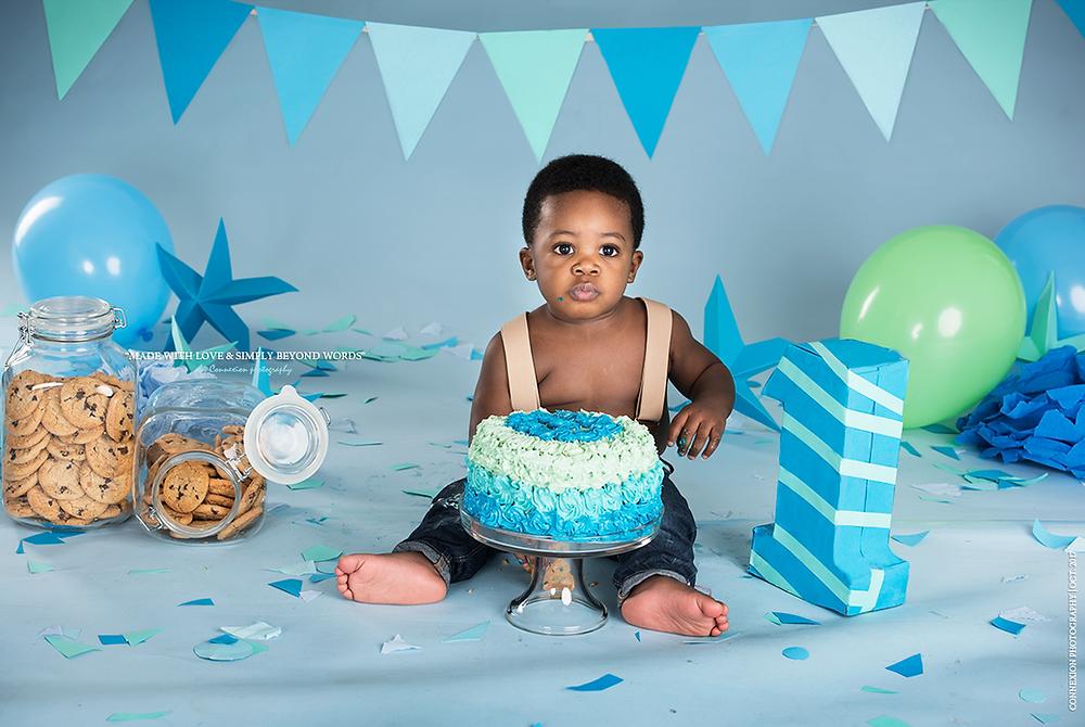 Enfant noir habillé en salopette assis dans un décor d'anniversaire son gâteau entre les jambes