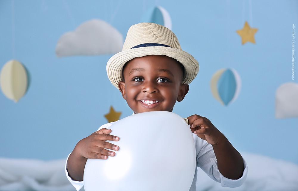 enfant noir assis dans un décor sur fond bleu tient un ballon entre ses mains et sourit