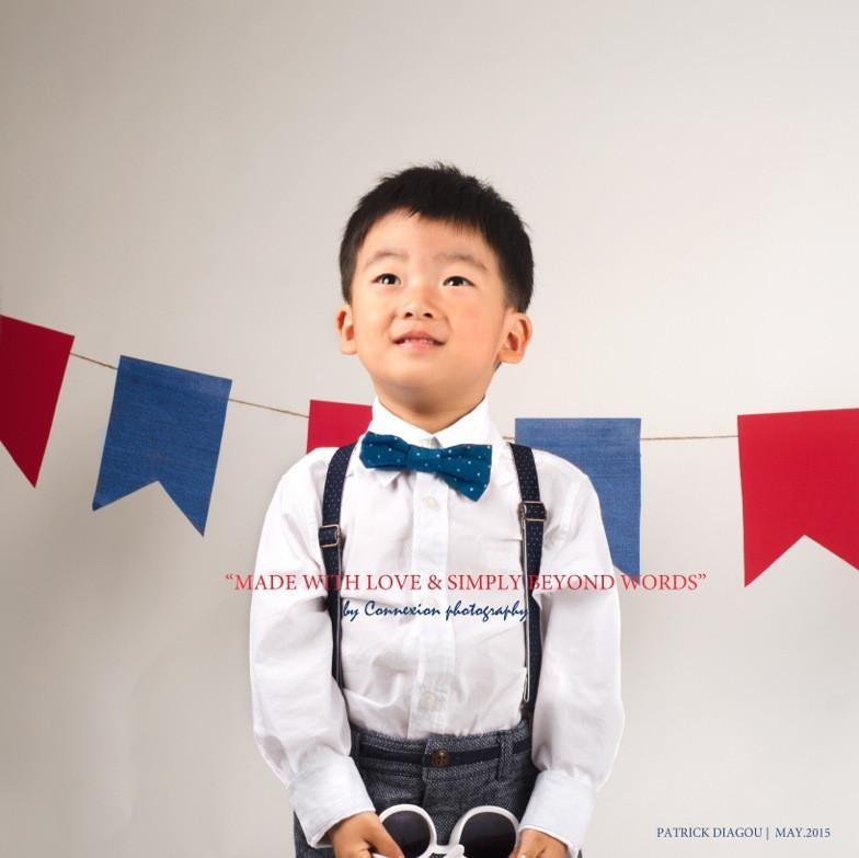 Enfant asiatique debout sur le sol en tenue de soirée avec des lunettes de soleil entre les mains