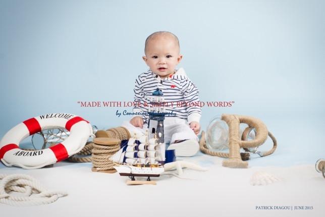 Bébé blanc en tenue de marin à rayures noirs et blancs assis avec  fond bleu et une décoration marine