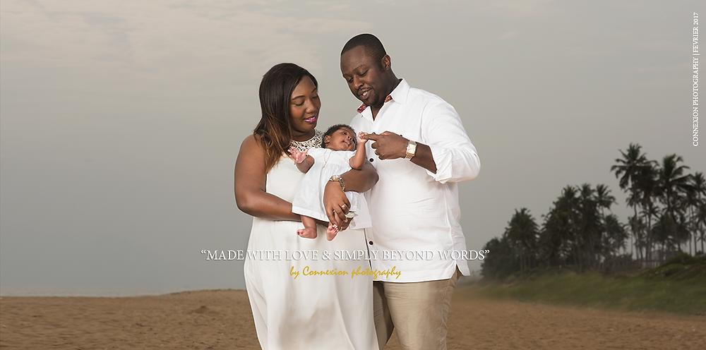 famille noire debout bord de mer papa et maman regarde bébé dans bras de maman
