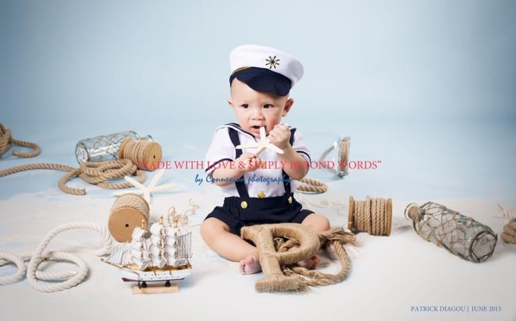 Bébé blanc en tenue de marin avec képi, étoile de mer dans la bouche, assis dans un décor de marin sur fond bleu