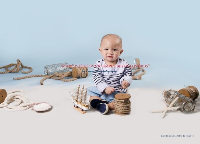 Bébé blanc en tenue de marin à rayures blanches et noires, souriant , assis dans un décor marin avec fond bleu
