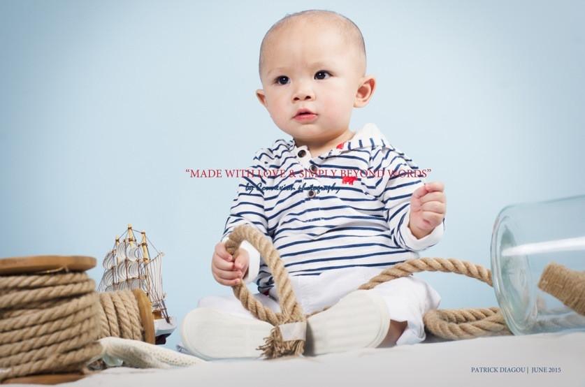 Bébé blanc en tenue de marin à rayures blanches et noires  assis, corde à la main  sur fond bleu avec une décoration marine