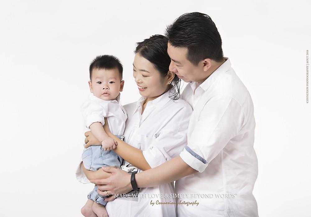 famille asiatique debout sur fond blanc avec leur enfant dans les bras de maman