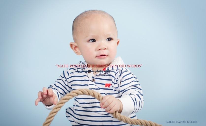 Bébé blanc en tenue de marin à rayures blanches et noires assis, corde à la main sur fond bleu