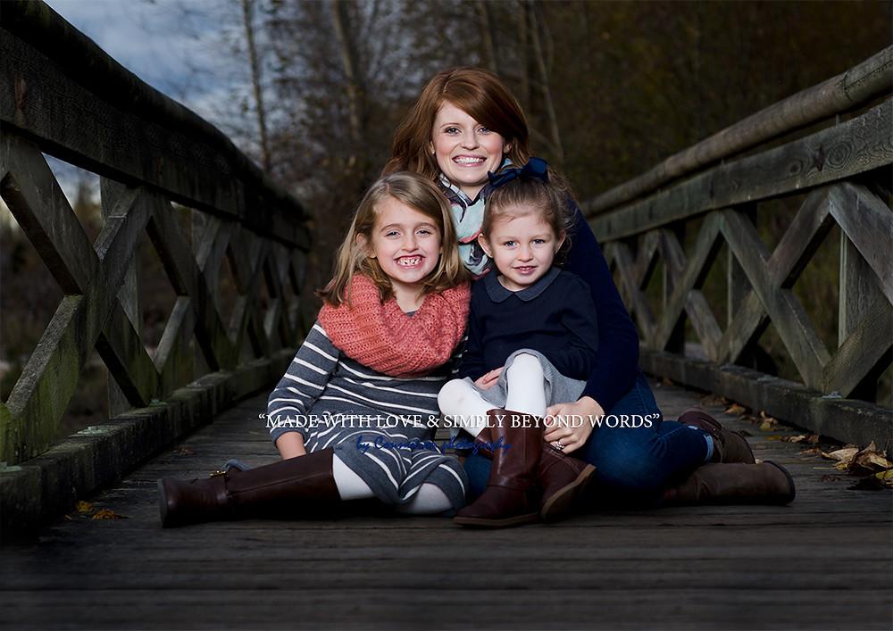maman et ses deux fille blanches assises sur un ponton
